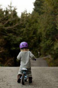 Seguro para bicicletas - Imagen de una niña vista de espalda subida a su bicicleta en un camino