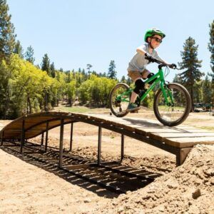 Seguro Bicicleta - Imagen de un niño con casco pasando con su bicicleta por un mini puente de madera
