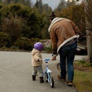 Seguro bici - Imagen de una madre ayudando a su hijo a llevar una bicicleta