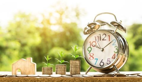 Seguro para bicicletas - Imagen de 3 pilas de monedas ordenadas de menor a mayor segun su altura y un reloj despertador a un lado ilustrando la idea de inversión o ahorro en el tiempo