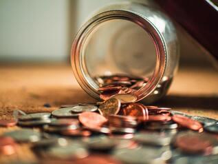 Seguro para bicicletas - Imagen de un frasco lleno de monedas que se tumba sobre una mesa