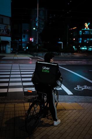 Seguro para bicicletas - Imagen de un ciclista trabajando de delivery por las calles de la ciudad nocturna
